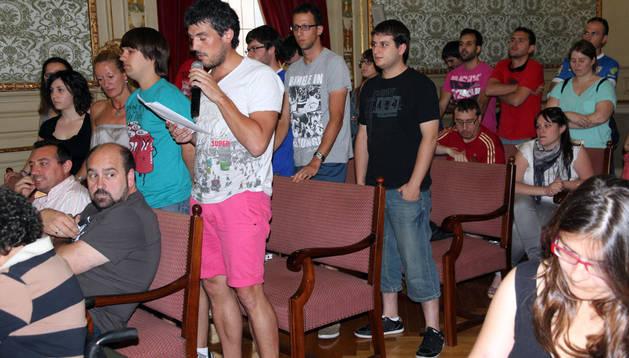 Iñaki Arriazu, con el micrófono, interviene en el pleno junto a varios de los jóvenes que acudieron
