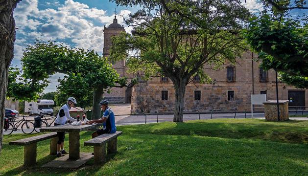 Dos turistas descansan en la zona verde de mesas que se sitúa frente al monasterio de Irache de Ayegui.