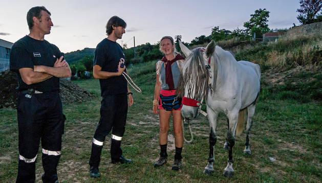 Andrea Mais, con su caballo, charla con dos bomberos del parque de Estella.