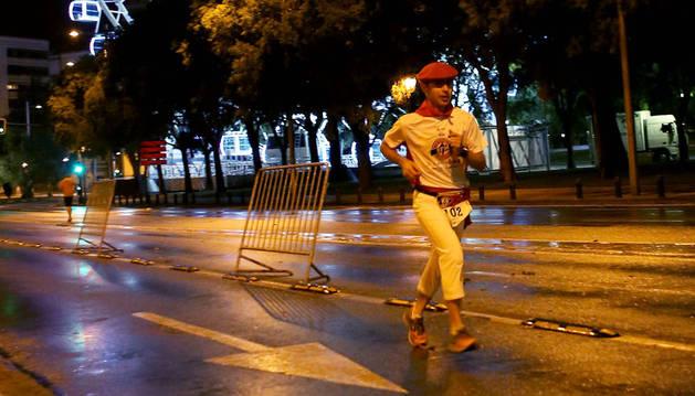 Olphand Jean Noël con el uniforme sanferminero pasa por delante de la noria en la calle Larraina en la esquina con San Roque