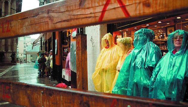 Un grupo de personas se protege de la lluvia para presenciar el encierro en la plaza consistorial.