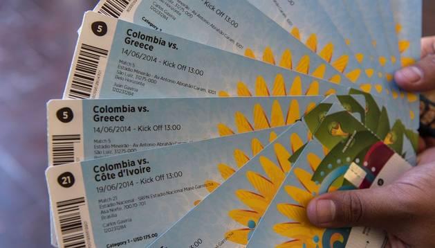 Una persona muestra varias entradas para partidos del Mundial de Brasil 2014