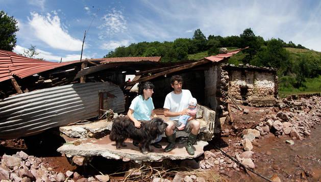 Patricia Tornero, Isidro Tapiz y su bebé Amets,  sentados en el caserío donde viven desde hace dos años, y que resultó gravemente dañado por la tromba de agua.