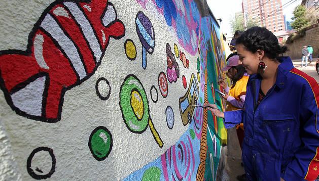 Funcionarias de la alcaldía pintan murales en 'la calle de la felicidad'