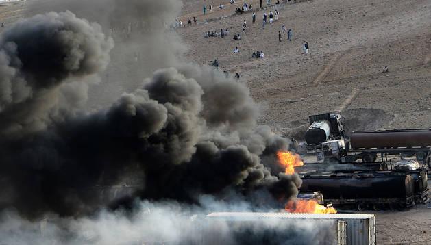 Columnas de humo ascienden al cielo por el incendio de los tanques de combustible