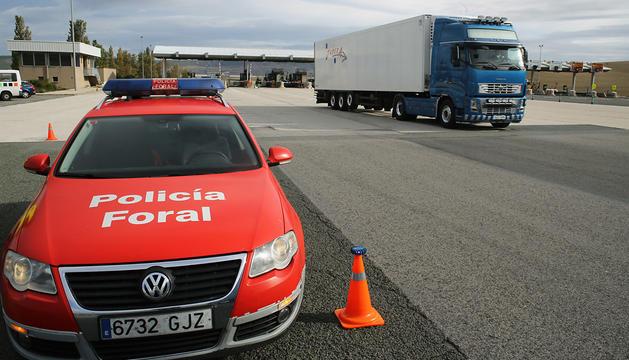 Vehículo de Policía Foral, detenido en el peaje de Imárcoain, por donde está circulando un camión.