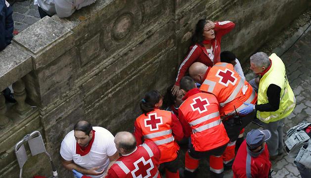 Efectivos de la Cruz Roja atienden a dos personas tras el quinto encierro