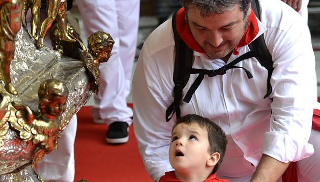 Un padre acerca a su hijo a San Fermín durante la ofrenda floral