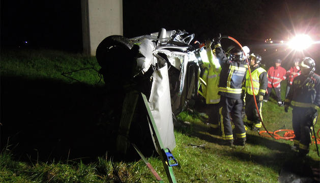 Los bomberos, junto al coche accidentado.