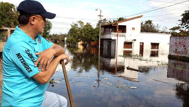 Un hombre, observando las calles inundadas del centro de Asunción