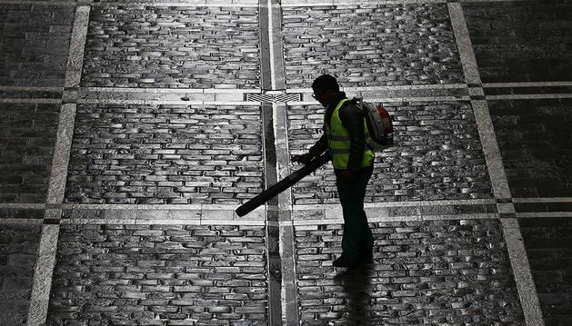 Un empleado de los servicios de limpieza barre con aire a presión el recorrido del encierro en la mañana del sábado 13 de julio
