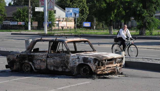 Un hombre pasea con su bicicleta junto a un coche quemado en Lugansk.
