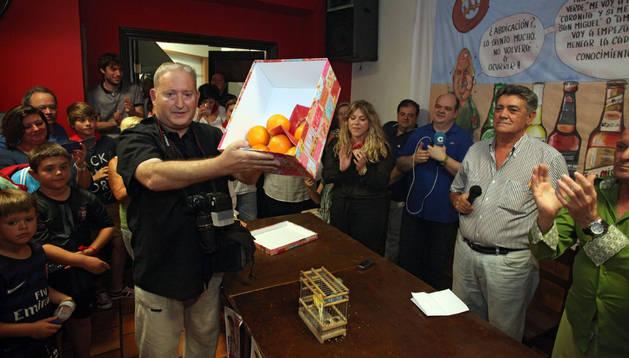 Jesús Marquina, rodeado de asistentes al acto, con el premio Naranja de la peña La Teba