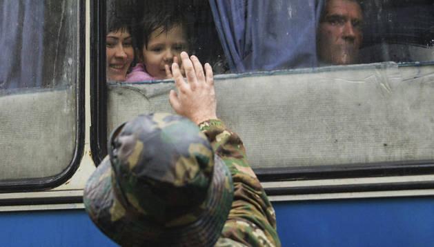Un soldado prorruso se despide de su familia mientras residentes y familiares de los militares porrusos parten a Rusia desde Donetsk (Ucrania)
