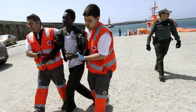 Dos miembros de la Cruz Roja atienden a un inmigrante interceptado en un bote a remos