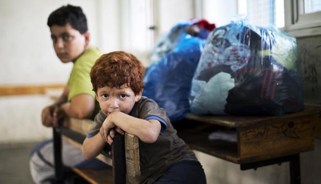 Un niño espera en una de las instalaciones de la ONU tras haber sido evacuado de su casa.