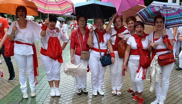Varias mujeres con paraguas el día del Chupinazo.