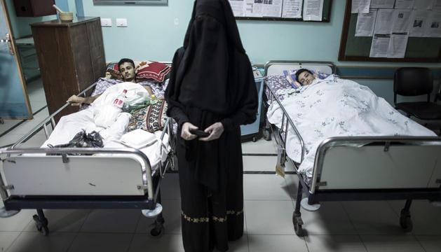 Una activista feminista visita a dos pacientes que descansan en sus camas en el pasillo del hospital Al Wafa en Gaza
