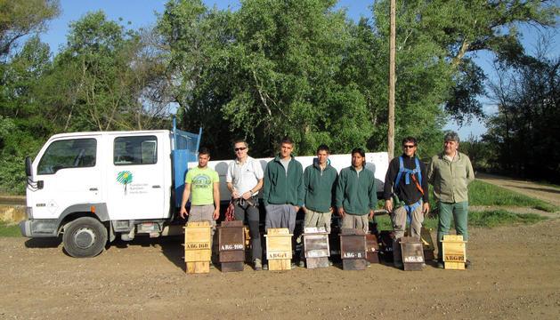 Jóvenes de la fundación donde se han construido las cajas-nido, con algunas de ellas y el alcalde, Fernando Mendoza, a la derecha.
