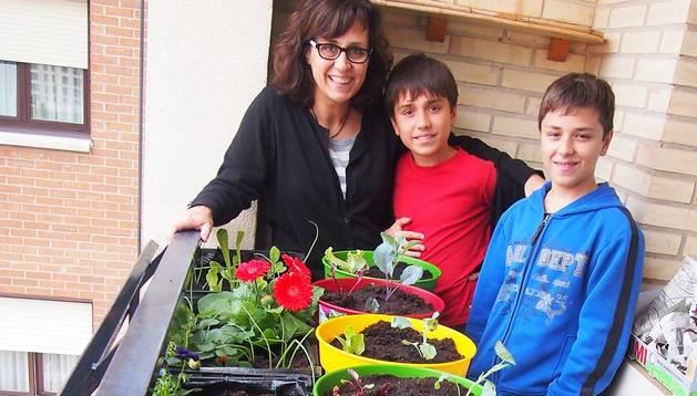 María José Aguas Aranguren con sus hijos, Joseba (a su lado) y Samuel, donde se combina la ornamentación floral con variedades de lechugas, acelgas y fresas