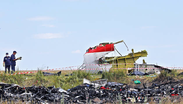 Dos personas recogen datos junto a los restos del avión en las proximidades de Grabovo