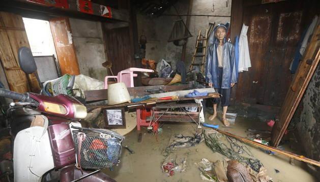 Un granjero posa en su casa en la provincia de Hainan, destruida por el tifón Rammasun
