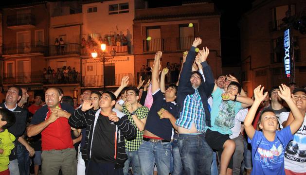 Varios jóvenes saltan a la vez para intentar hacerse con las peras lanzadas desde uno de los balcones de la plaza de los Fueros.