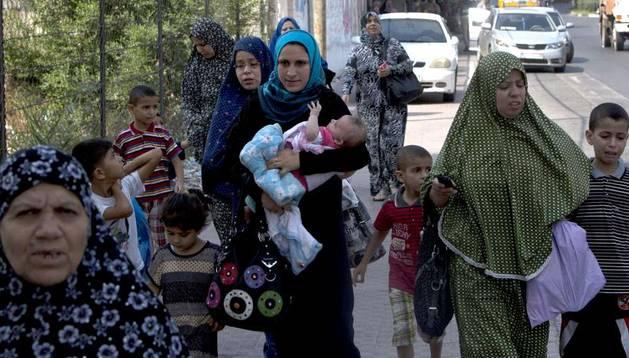 Un grupo de palestinos evacúan sus casas tras recibir un aviso de ataque