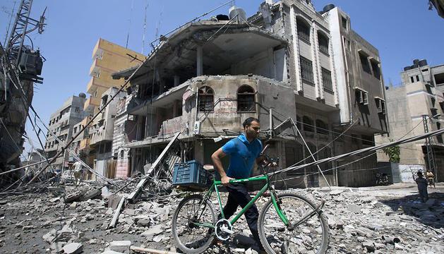 Un palestino camina entre los escombros de las viviendas de la ciudad de Gaza
