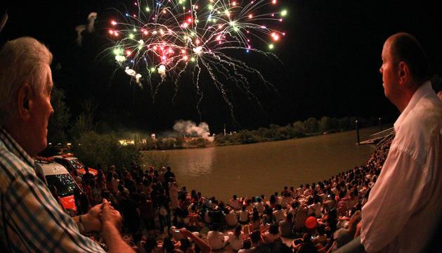 Un grupo de personas observa los fuegos. Al otro lado del río se aprecia el punto de lanzamiento.