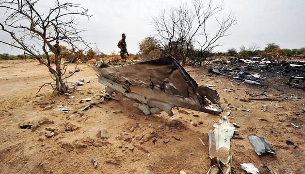 Un soldado francés, entre los restos del avión