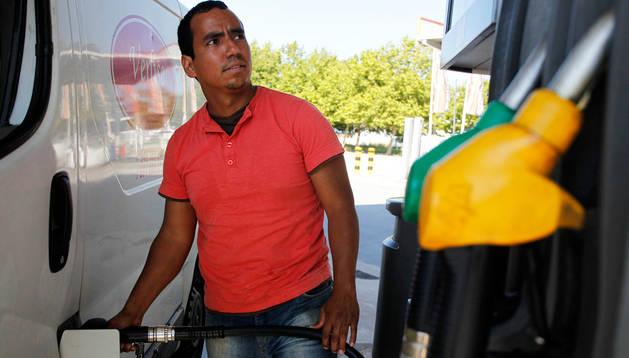 Antonio García llena el depósito de su furgoneta mientras comprueba el importe que marca el surtidor