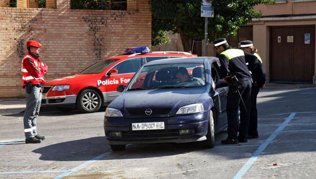 Un Policía Foral y una pareja de policías municipales piden la documentación al conductor de un vehículo en un control policial en Tudela