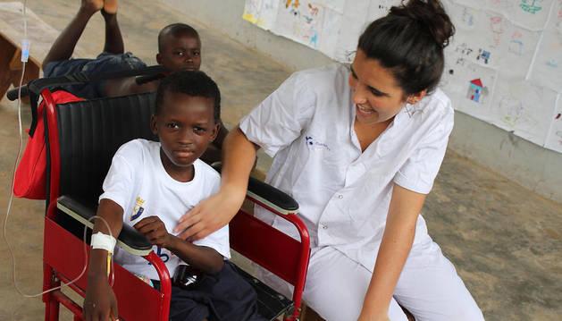 Marta Alústiza Zavala, alumna de 3º de Medicina de la Universidad de Navarra, con Henry, un paciente de 8 años, en 2013.