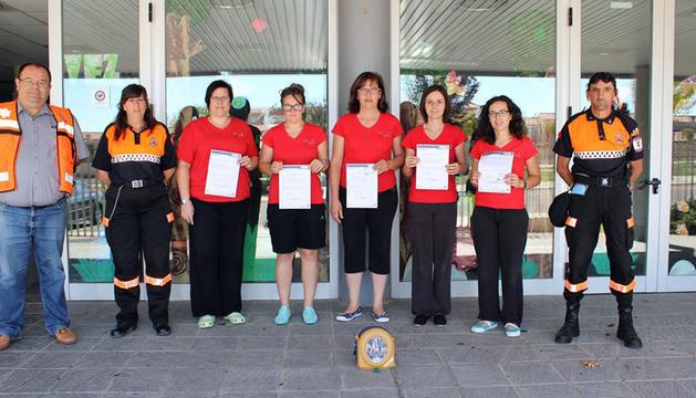 Las trabajadoras del centro, con sus diplomas, junto a Protección Civil.