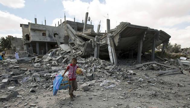 Un niño lleva un balón y una jaula entre las ruinas de los edificios en Gaza