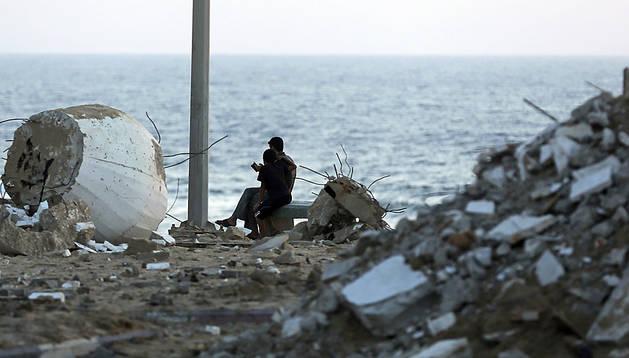Dos palestinos descansan sobre los escombros en Gaza