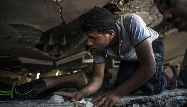 Un palestinos busca supervivientes entre los escombros de un edificio bombardeado