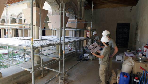 Técnicos revisan la documentación existente sobre los capiteles, que todavía están cubiertos con unas chapas de madera.