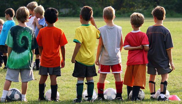 Varios niños, jugando al fútbol.