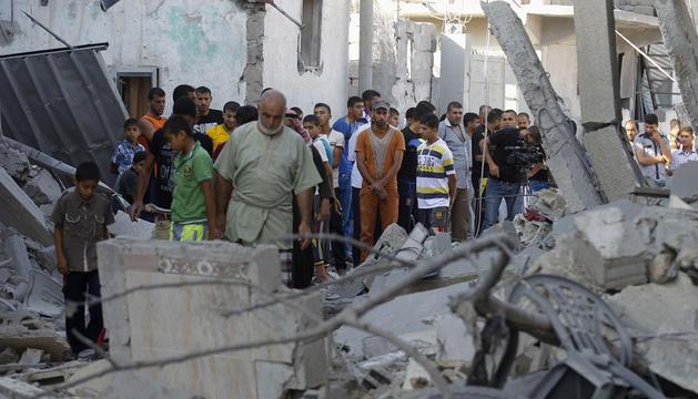 Un grupo de palestinos inspeccionan una casa destruida este domingo por Israel