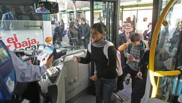 na chica sube al autobús y se dispone a pagar con una de las tarjetas sin contacto.