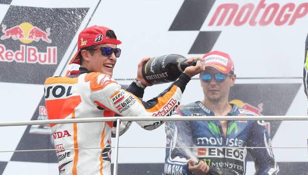 Márquez celebrando el triunfo con un cariacontecido Lorenzo al fondo
