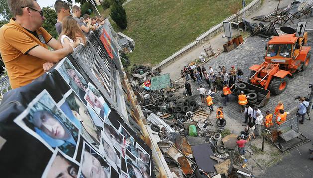 Varios ucranianos observan desde un puente en el que aparecen fotografías de las personas asesinadas durante las protestas de invierno mientras trabajadores municipales retirar las barricadas y escombros