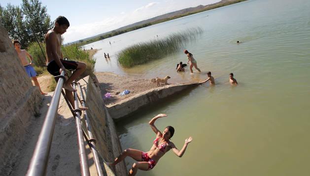 Una chica se lanza de espaldas a la balsa desde la casilla mientras la observan el resto de sus amigos y otras personas disfrutan de un baño en el agua.