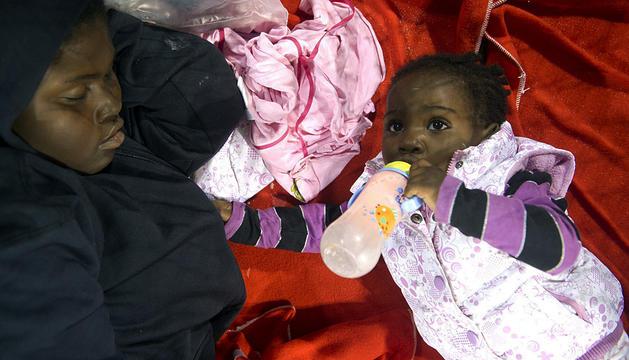 Una mujer descansa mientras su niña toma un biberón en Tarifa.