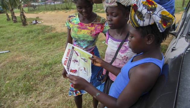 Varias mujeres liberianas leen un pasquín informativo sobre el virus del ébola en Monrovia (Liberia)