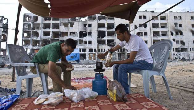 Dos hermanos palestinos preparan su desayuno.