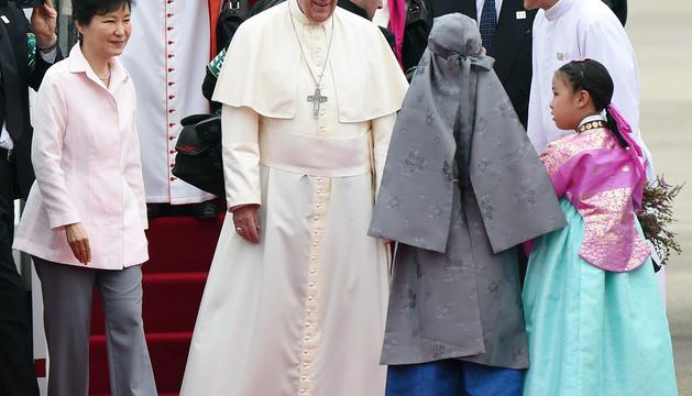 El papa Francisco recibe flores de una niña acompañado de la presidenta de Corea del Sur Park Geun-Hye.