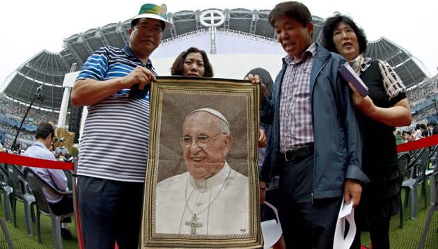Unas personas posan con una foto del pontífice Francisco I en Seúl.